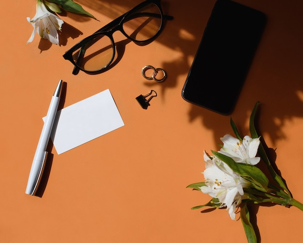 Рабочий стол домашнего офиса. женское рабочее пространство с макетом визитной карточки, ручкой, цветами, очками, серьгами, канцелярским зажимом. свет и тень на фоне имбиря. плоская планировка, вид сверху. фирменный стиль.