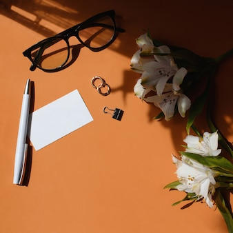 Home office desk. female workspace with business name card mock up, pen, phone, flowers, glasses, earrings, stationery clip. light and shadow on a ginger background. flat lay, top view.
