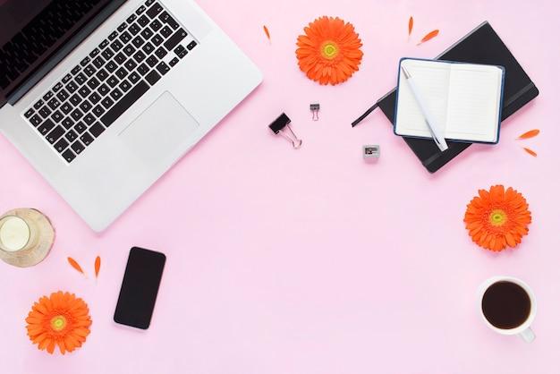 ホームオフィスデスク。ノートパソコン、電話、ペン、キャンドル、コーヒーマグ、ピンクの背景にオレンジ色の花と花びらと黒の日記と女性のワークスペース。フラットレイ、上面図。ファッションブログルック。