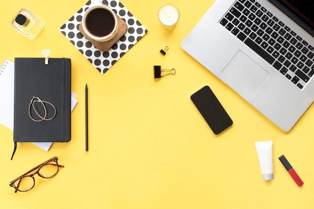 ホームオフィスデスク。ノートパソコン、電話、鉛筆、キャンドル、女性の化粧品アクセサリー、コーヒーマグ、黄色の背景に黒の日記と女性のワークスペース。フラットレイ、上面図。ファッションブログルック。