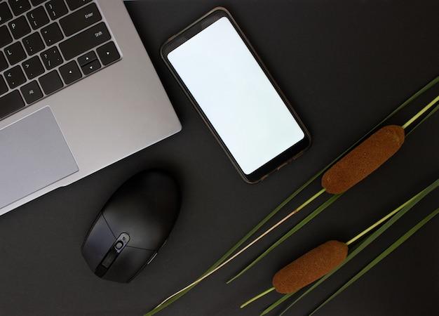 ホームオフィスデスクラップトップモバイルコンピュータマウスと暗い背景のスタイリッシュなワークスペース