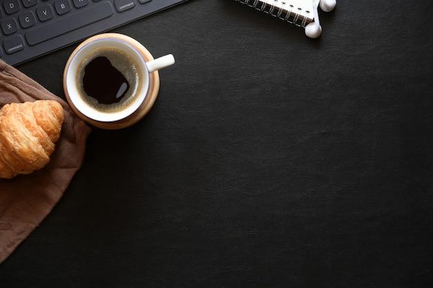 Место для домашнего офиса с кофе, круассаном и копией