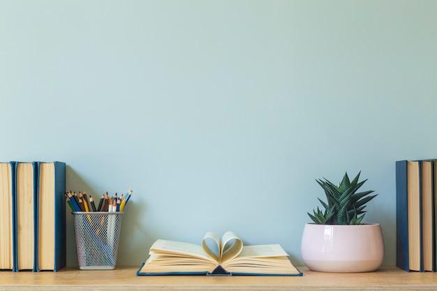 Предпосылка таблицы стола домашнего офиса. пустая стена с деревянным столом с канцелярскими принадлежностями и книгами для работы или учебы. фото высокого качества