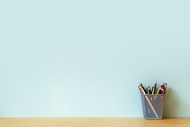 Предпосылка таблицы стола домашнего офиса. пустая стена с деревянным столом с канцелярскими принадлежностями, карандашами для работы или учебы. скопируйте пространство. фото высокого качества