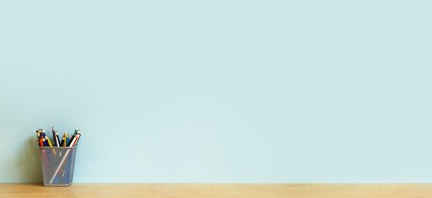 Домашний офис стол стол баннер фон. пустая стена с деревянным столом с канцелярскими принадлежностями, карандашами для работы или учебы. скопируйте пространство. фото высокого качества