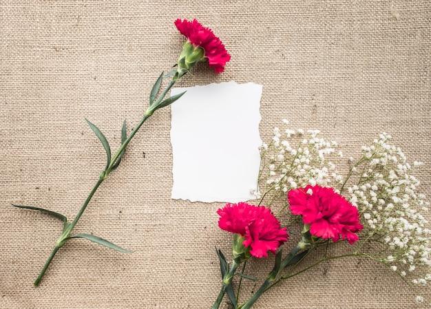 メモ用紙、荒布を着た花の花束とホームオフィスの机のテーブル