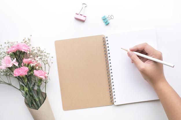 Стол стол домашнего офиса с рукой женщины, блокнотом, цветком на белой предпосылке.