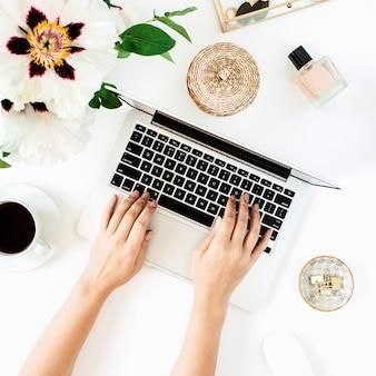 Рабочий стол стол домашнего офиса с ноутбуком и цветами на белой поверхности