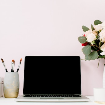 Home office desk with blank screen laptop, beautiful roses and eucalyptus bouquet, white vintage casket in front of pale pastel pink