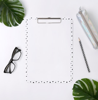 Home office desk with clip board, glasses, pencil case, green leaves and pensil.