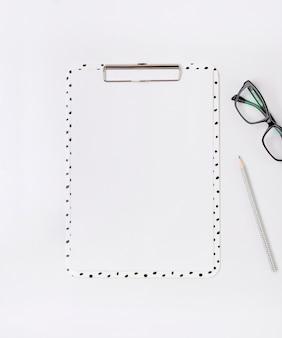 Home office desk with clip board, glasses, pensil.
