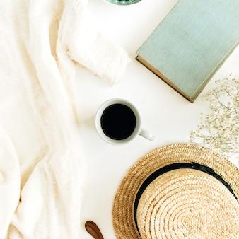 Стол домашнего офиса с кофе, книгой, соломенной шляпой и одеялом на белой поверхности