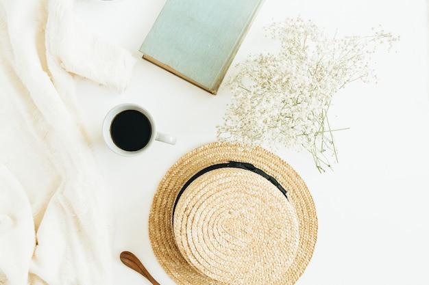 Стол домашнего офиса с кофе, книгой, соломенной шляпой, цветами и одеялом на белой поверхности. плоская планировка, вид сверху