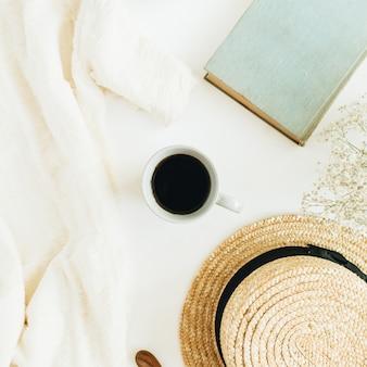 Стол домашнего офиса с кофе, книгой, соломенной шляпой, цветами и одеялом на белой поверхности