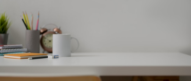 Home office desk with copy space, coffee mug, diary notebooks, stationery and decorations
