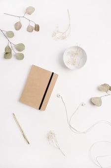 공예 일기, 펜, 헤드폰 및 흰색 바탕에 유칼립투스 가지와 홈 오피스 책상. 평면 위치, 평면도
