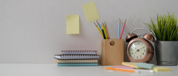 Home office desk with diary notebooks, stationery, decorations and copy space on white desk