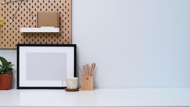 Стол домашнего офиса с пустой рамкой для фотографий, кофейной чашкой, комнатным растением и держателем для карандашей.