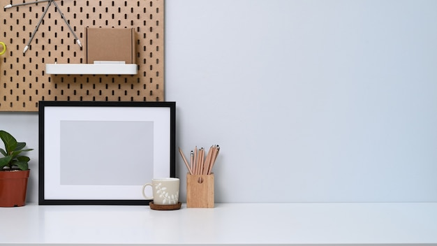 Home office desk with empty photo frame, coffee cup, house plant and pencil holder.