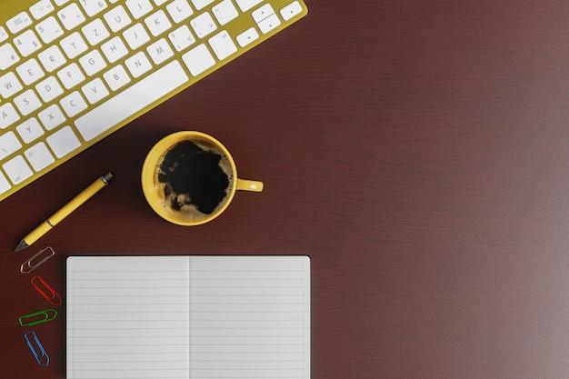 Стол домашнего офиса с тетрадью, желтой ручкой, желтой клавиатурой и желтой чашкой кофе на красной деревянной таблице. вид сверху плоская планировка с копией пространства.
