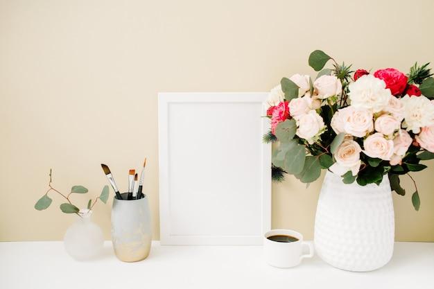 창백한 파스텔 베이지 배경 앞의 사진 프레임, 아름다운 장미와 유칼립투스 꽃다발이있는 홈 오피스 데스크