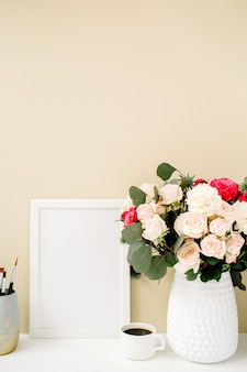 Home office desk with photo frame mock up, beautiful roses and eucalyptus bouquet in front of pale pastel beige background