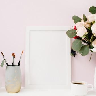 淡いパステルピンクの前にフォトフレームのモックアップ、美しいバラとユーカリの花束とホームオフィスデスク