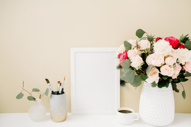 Home office desk with photo frame mockup, beautiful roses and eucalyptus bouquet in front of pale pastel beige