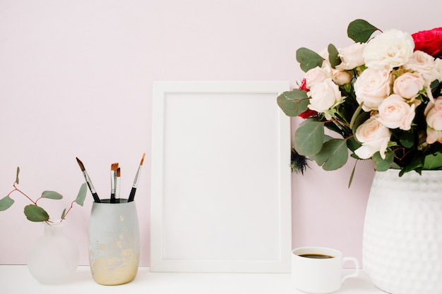 Home office desk with photo frame mockup, beautiful roses and eucalyptus bouquet