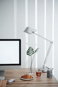 Рабочий стол домашнего офиса с чаем и свежим круассаном на завтрак рядом с экраном компьютера и вазой с листьями