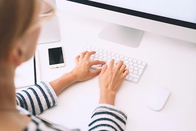 ホームオフィスデスク。女性のワークスペース。コンピューターのキーボードでテキストを入力する女性の手。上面図、モックアップ。