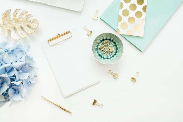 白地に白紙クリップボード、アジサイの花の花束とホームオフィスデスクワークスペース。フラットレイ、上面図のモックアップ。