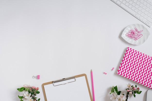 コピースペースと白い背景の上の白紙クリップボード、メモ帳、キーボード、文房具、リンゴの木の花とホームオフィスデスクワークスペース。フラットレイアウト、上面図