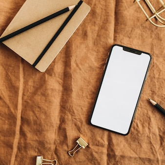 茶色の毛布に空白の画面のスマートフォンとホームオフィスのデスクのワークスペース。フラットレイ、トップビューの最小限のブログヒーローヘッダー。