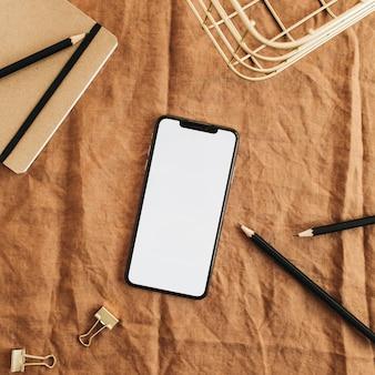 茶色の毛布に空白の画面のスマートフォンとホームオフィスデスクワークスペース。フラットレイ、上面図