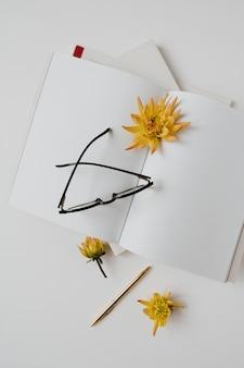 빈 시트 노트북, 안경, 흰색 테이블에 꽃 홈 오피스 책상 작업 영역. 평면 평신도, 평면도. 여자, 여자 보스 작업 또는 비즈니스