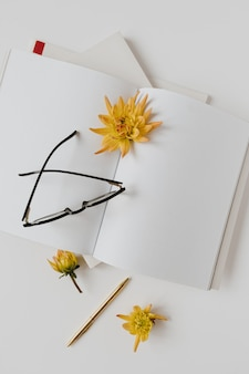 Рабочее пространство стола домашнего офиса с тетрадью чистого листа, стеклами, цветками на белой таблице. плоская планировка, вид сверху.