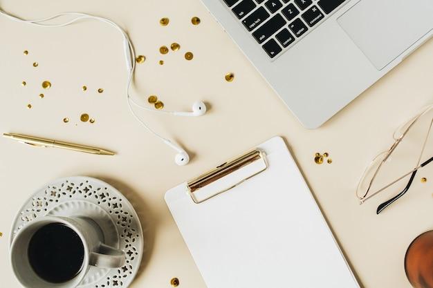 Рабочий стол домашнего офиса с буфером обмена, ноутбук, кофе на бежевом