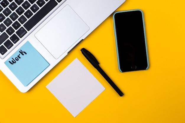 Место для работы стола домашнего офиса с стикером компьтер-книжки и бумаги на желтой предпосылке. деньги, диаграмма, граф дом квартира, вид сверху работа бизнес-концепция. концепция работы на дому по карантину коронавируса