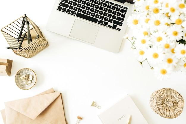 Рабочий стол домашнего офиса с ноутбуком, букет цветов ромашки и блокнот на белом