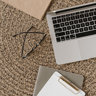 ラップトップ、クリップボード、わら籐のメガネとホームオフィスデスクワークスペース。