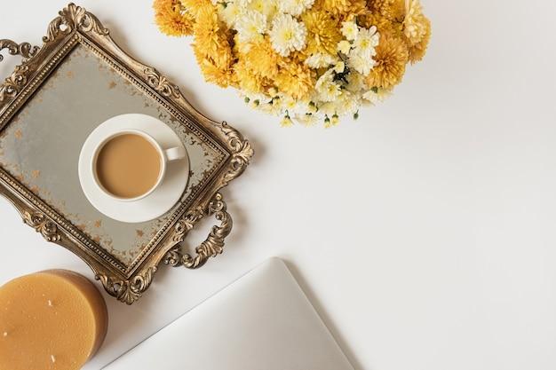 ノートパソコン、コーヒーカップ、ビンテージトレイ、秋の野花の花束とホームオフィスデスクワークスペース。フラットレイ、上面図