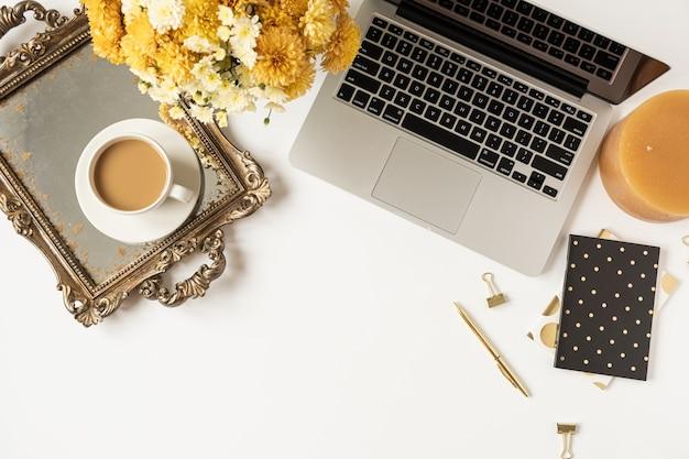 ノートパソコン、コーヒーカップ、ビンテージトレイ、白い背景の上の野花の花束と秋のホームオフィスデスクワークスペース。フラットレイ