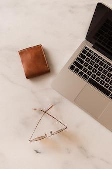 ノートパソコン、メガネ、大理石のテーブルの財布とホームオフィスデスクワークスペース