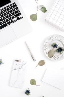 ノートパソコンを備えたホームオフィスの机のワークスペース、大理石のケースを備えた携帯電話、ペン、紙、ノート、白い背景にユーカリの枝。上面図。