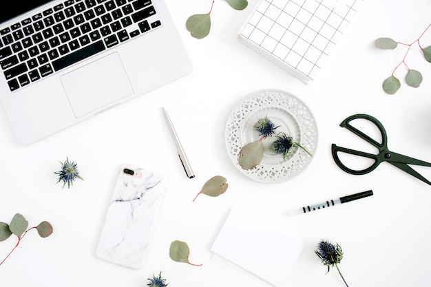 Home office desk workspace with laptop, mobile phone with marble case, pen, paper, notebook and eucalyptus branches on white background
