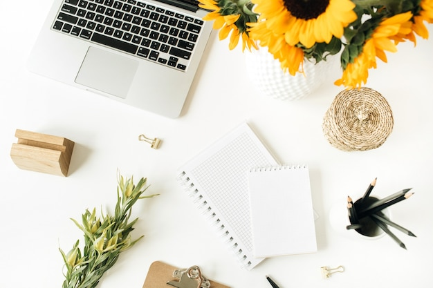 Home office desk workspace with laptop, notebook, clipboard, yellow sunflowers bouquet on white