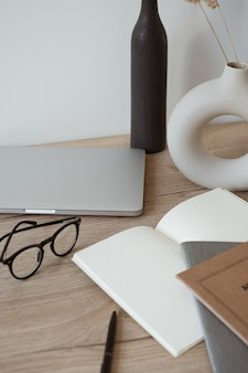 Home office desk workspace with laptop, notebook, glasses on wooden