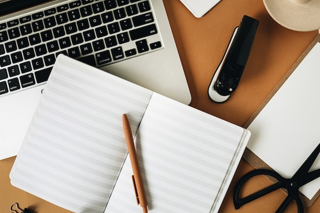 Рабочий стол домашнего офиса с ноутбуком на имбирной поверхности