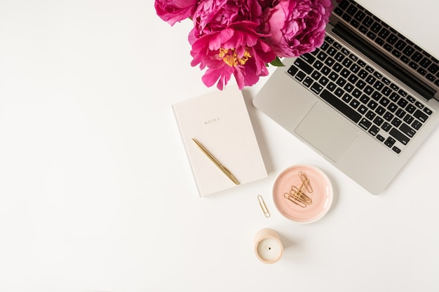 Home office desk workspace with laptop, pink peony flowers bouquet and notebook on white. flat lay, top view